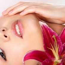 woman lying down with flower under her chin
