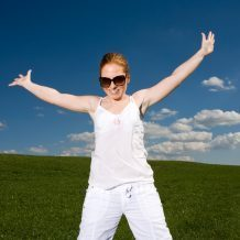 woman standing in grassy plain throwing her arms back