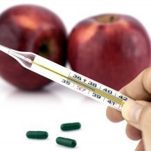 hand holding thermometer with apples and supplements in background