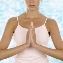 woman clasping hands in front of her in namaste pose