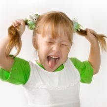 little girl pulling her pigtails and making a face