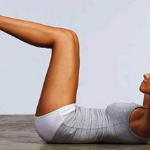 woman lying on ground doing crunches