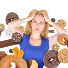 woman overwhelmed by cookies, doughnuts, and other delicious junk food