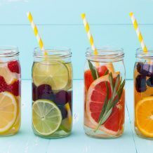 jars of water with different types of fruit and citrus in each