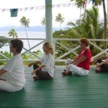 people meditating on patio by beach