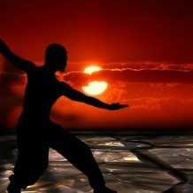 silhouette of person doing tai chi at sunset