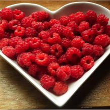 heart shaped dish filled with raspberries
