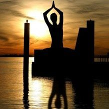 silhouette of person meditating over water
