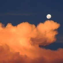 moon in sky with bright orange clouds