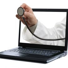 doctor's hand holding stethoscope coming out of computer screen