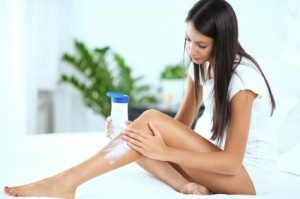 Woman applying lotion to her leg beauty habits