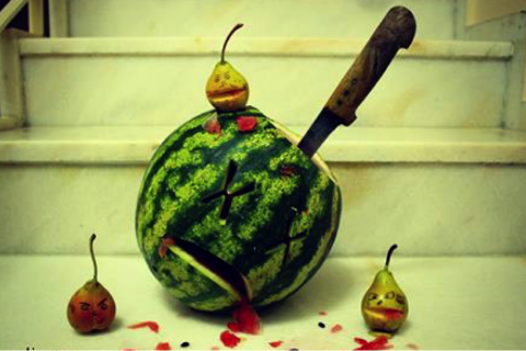 Watermelon stabbed with knife with x's for eyes