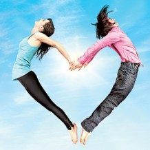 two people jumping up and forming a heart with their bodies