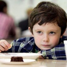 Young kid sitting at lunch table with malnutrition