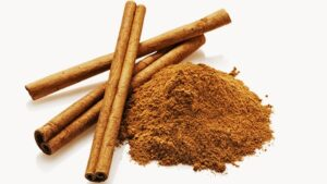 Cinnamon Sticks Next to a Pile of Ground Cinnamon