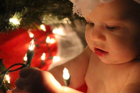 Baby holding lights under a Christmas tree