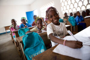 young children sitting at school desks with their backpacks from UNICEF next to them