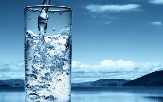 A glass being filled with water surrounded by a lake and a mountain scape.