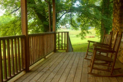Two rocking chairs on a porch looking out at a forrest.