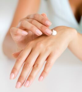 Womans hand with cream about to be rubbed in on the top of her palm