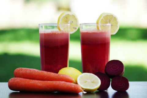 pressed juices with carrot, beet, and lemon wedges