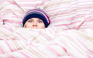 Scared Woman in Beanie Hat Hiding Under Bed Covers