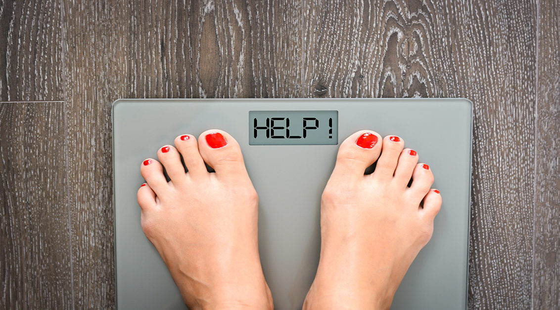 Feet Standing on a Scale that says Help for the Weight