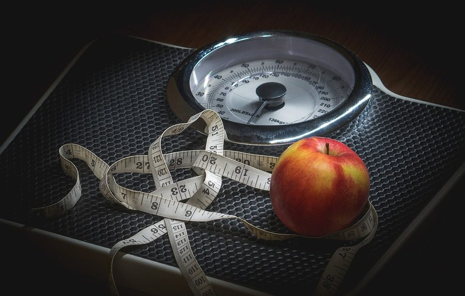 scale with measuring tape and a red apple on top of the scale