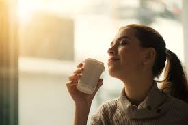 Woman drinking hot beverage from white cup