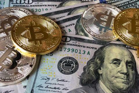 Gold and Silver Bitcoin Currency placed in top of a U.S.A $100 Bill