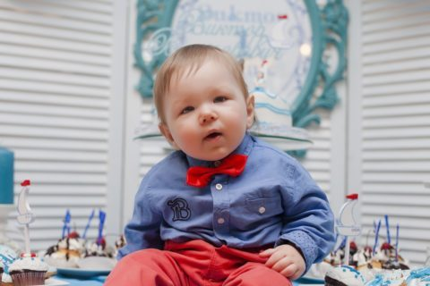 Blonde Baby in Blue Button Down Shirt with Red Bow Tie and Red Pants at a New Year's party