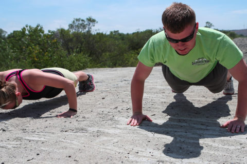 A man and a woman on a beach doing pushups