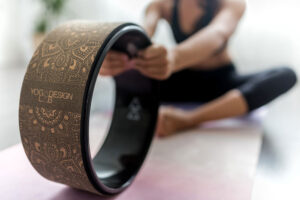 woman stretching using a luxury yoga Mandala cork wheel