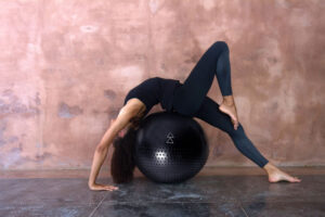 woman stretching on black luxury yoga ball