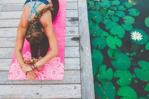 woman stretching on pink luxury yoga mat near lily pads