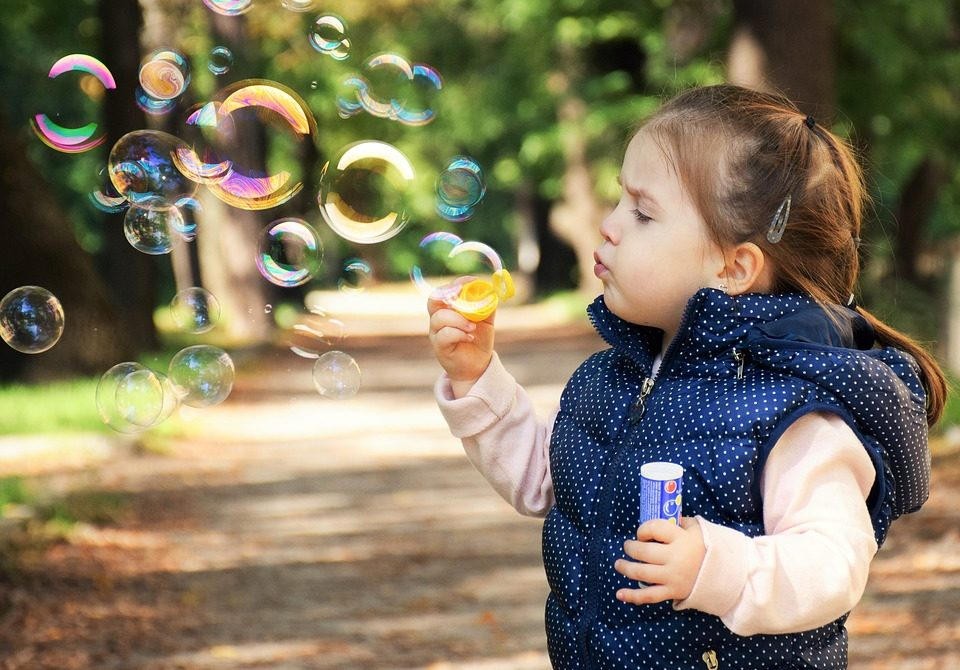 little brown haired girl in a light pink sweater and a navy colored vest with white polka dots blowing bubbles in a park full of tall trees