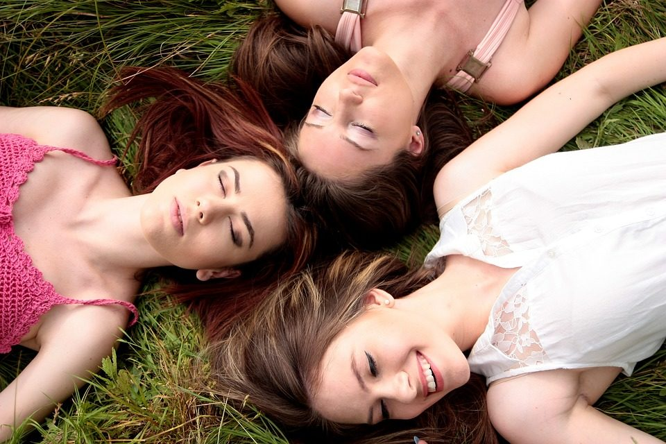 three girls with brown hair lying on top of green grass smiling