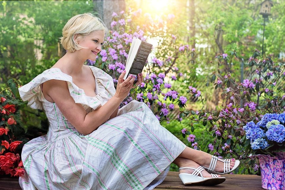 women with short blonde hair dressed in a white dress with pink and green vertical stripes with white wedge heels reading a book in a flower garden.