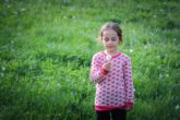 little girl in a light pink sweater with bright pink hearts standing in the middle of a green field blowing on a dandelion