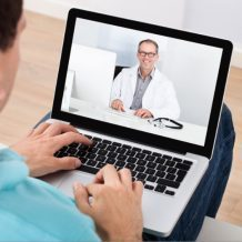 guy talking to doctor over computer webcam