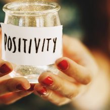 "hands holding a jar labeled ""positivity"""
