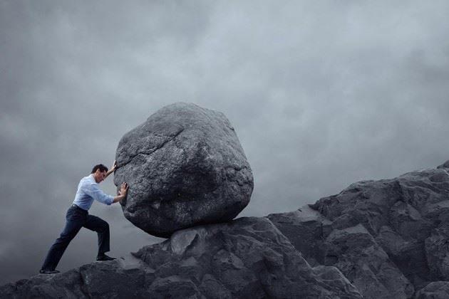 Man pushing boulder uphill