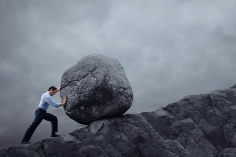 Man pushing boulder uphill