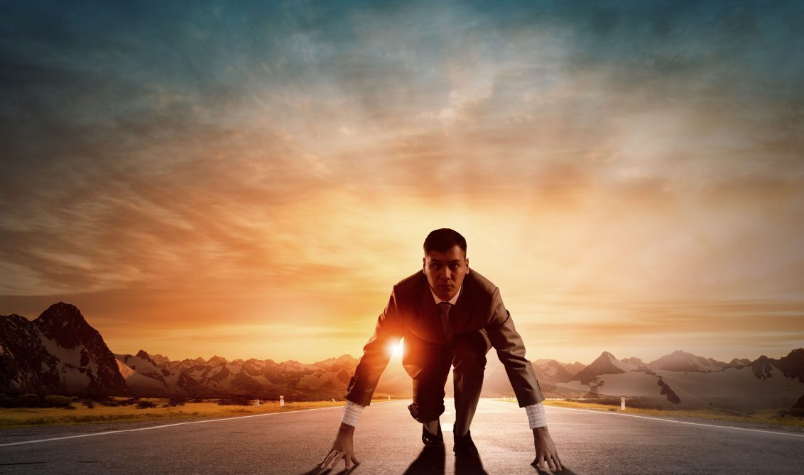Man in suit ready to run at sunrise