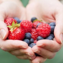 hands holding berries healthy skin no sun damage