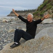 Older gentleman sitting on rocky beach with arms thrown out