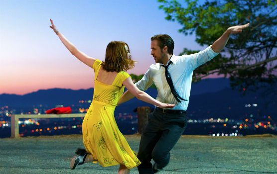Emma stone in a yellow dress dancing with Ryan Gosling.
