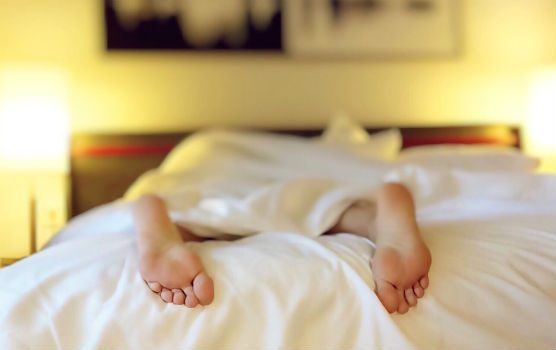 Person's feet sticking out at the end of the bed