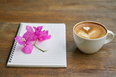 Chai Tea Latte and Notebook with Pink Flower on Wooden Table