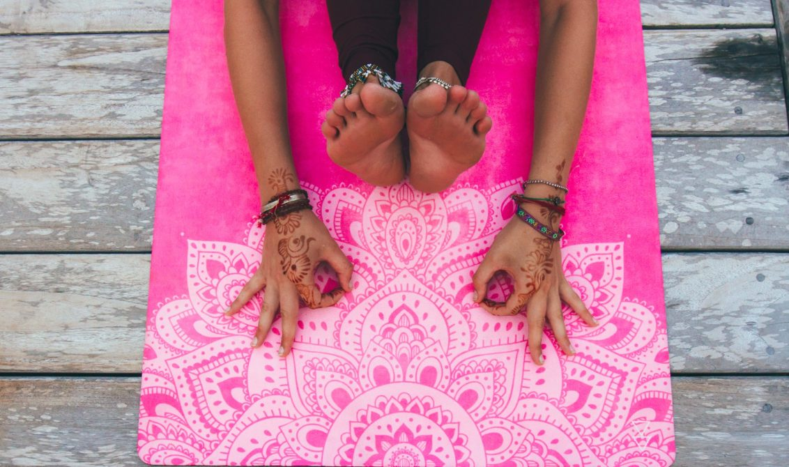 woman stretching on pink luxury yoga mat
